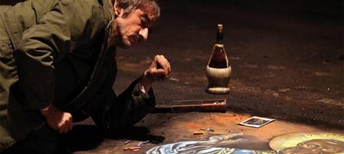 Un pintor callejero dibuja con tiza sobre el suelo romano (Fotograma de la pelicula).